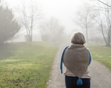 Woman in a stylish knitted cape and scarf combination walking along a misty winter road away from the camera in an healthy outdoor active lifestyle concept