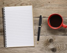 Coffee cup and notepad with pen on wooden table