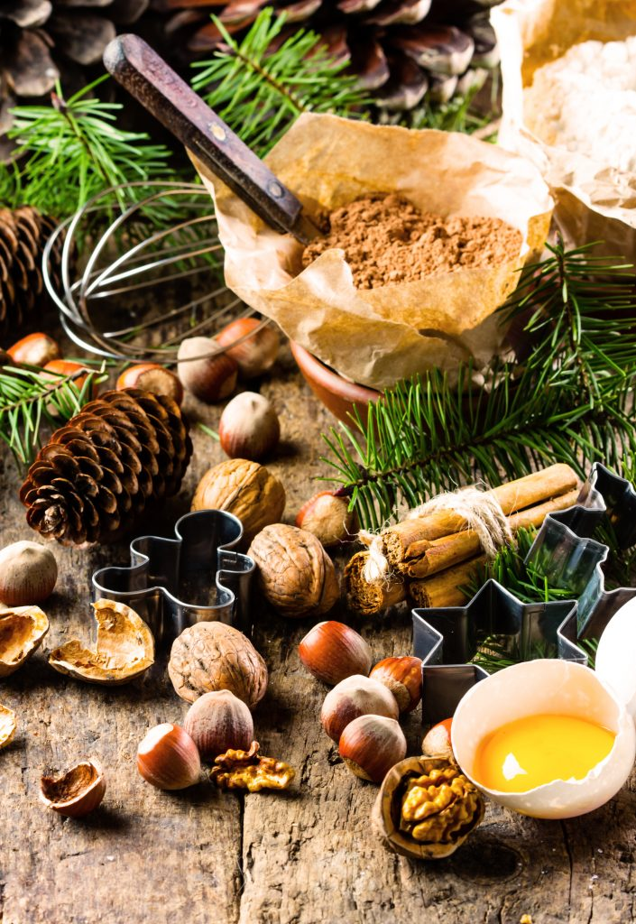 Christmas or New Year baking cake background. Dough, dough ingredients - flour, chocolate, walnuts, hazelnuts, sugar eggs cinnamon and Christmas decorations on wooden rustic background