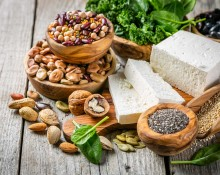 Selection of vegan plant protein sources - tofu, quinoa, spinach, broccoli, chia, nuts and seeds, wood background