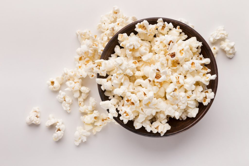 Wooden rustic bowl of popcorn isolated on white background, top view. Fast food, cinema snack and entertainment concept, cutout